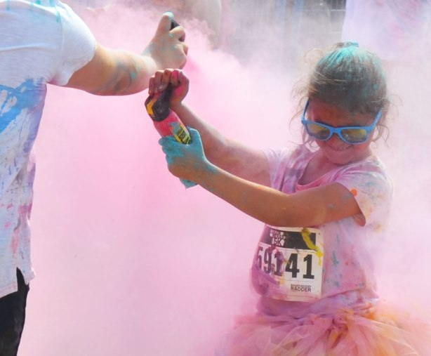 A young girl in a frilly tutu and blue sunglasses is holding a spray can of colour and she is spraying the people around her.