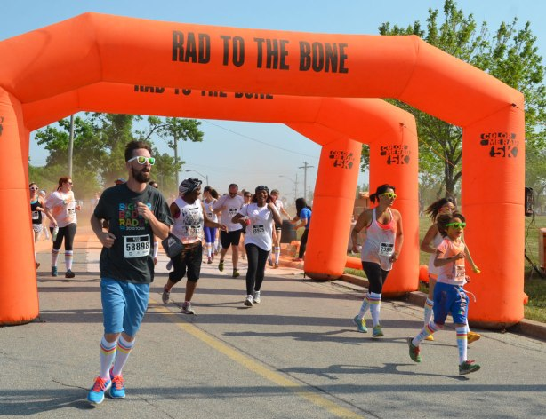 color me rad run, runners running under three inflatable orange banners