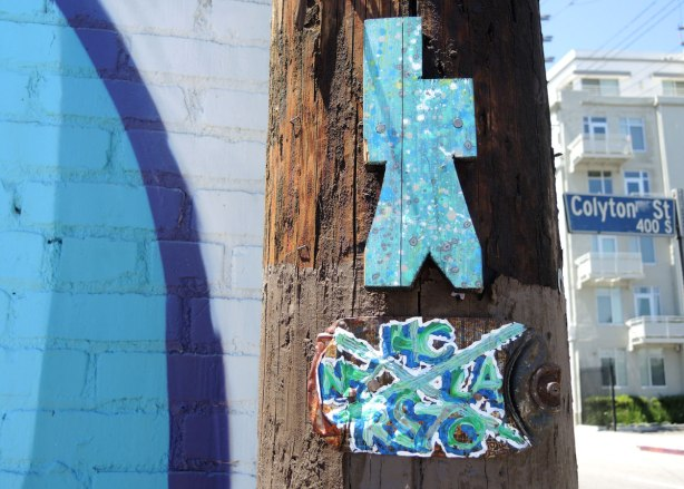 Two small bits of street art on telephone pole, a turquoise wood cut out that has a vaguely human shape as well as a piece, also in blues, with an X in the middle, and letters written in each quadrant of the X, NC on the top, LA on the right, RS70 on the bottom and NY on the left.
