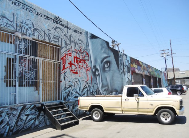 "An old pale yellow pick up truck is parked in front a mural that includes the words ""Her eyes like emotion sensors"""