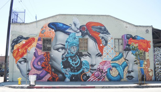 street art in the Arts District of LA (Los Angeles) - many women's faces with other creatures like a snake and a white dove, and things like guns and flowers,as well