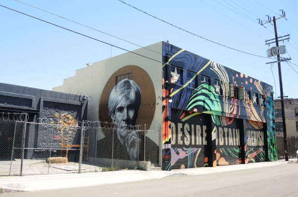 A large building with 3 large garage doors.  Each door has a word painted on it, desire, obtain, cherish.  A large street art painting surrounds the words - swirls and stars.  Part of the side of the building also has street art - a large black and white painting of Andy Warhol.