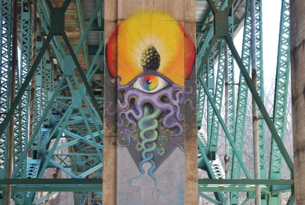 graffiti on the concrete supports under a bridge - large symbol with eye, yellow sun and serpent like shapes, high on a pillar up near the green metal girders of the bridge