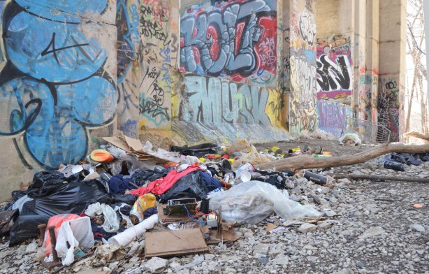 graffiti on the concrete supports under a bridge - a pile of trash beside graffiti covered sections of the bridge