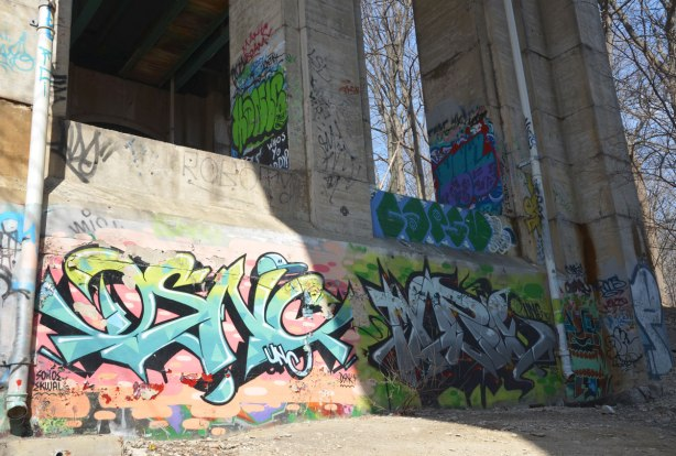 graffiti on the concrete supports under a bridge - colourful tags.  Some are older and are starting to peel