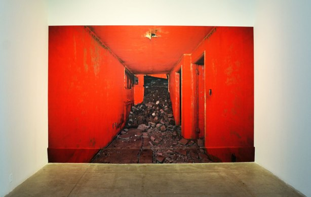 A large photograph of the inside of an abandoned building.  The interior walls have been painted red.  Rubble has started spilling into the hall from the demolition of the rest of the building.