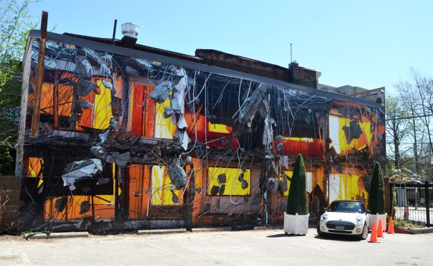 A large photograph (30 feet long) that covers the side of a building.  The photo is of a building being demolished.  It is to scale with the real building.