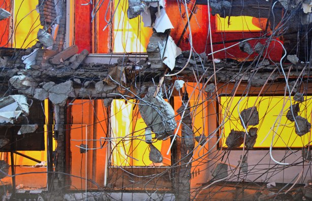 A close up of A large photograph (30 feet long) that covers the side of a building.  The photo is of a building being demolished.  It is to scale with the real building.