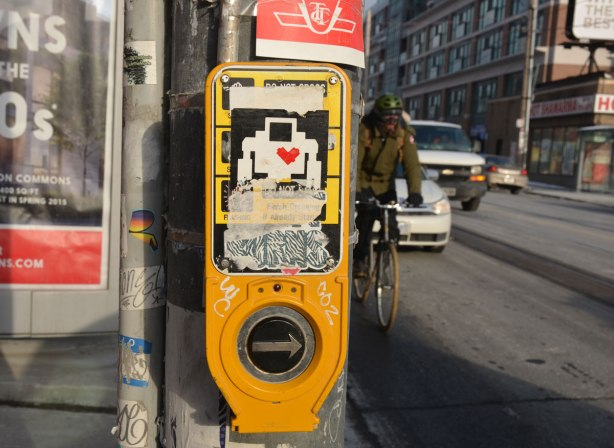 lovebot sticker on a yellow sign by the button one pushes when one wants to cross at a streetlight.