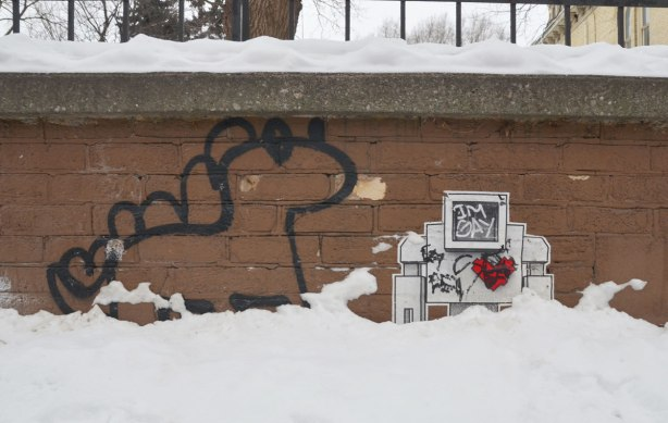 lovebot on a low brick wall, in the snow.  A black line drawn dinosaur is beside him.  Someone has scribbled 'I'm gay' on the lovebot