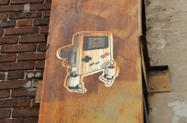 gameboy lovebot on a metal wall that has become rusty