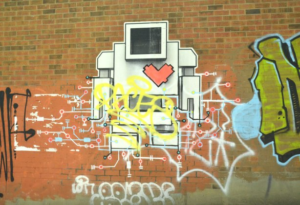 A large lovebot on a brick wall on Dundas West.  Included is a circuit drawing (electrical) around him.