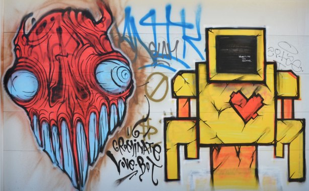 A graffiti painting on a white garage door, a yellow lovebot with red heart and a red face grominator with blue eyes and blue mouth and teeth
