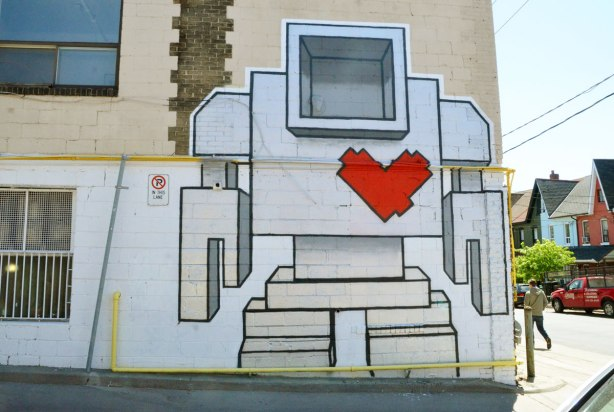 a very large lovebot painted on a wall.  He is close to two storeys tall.