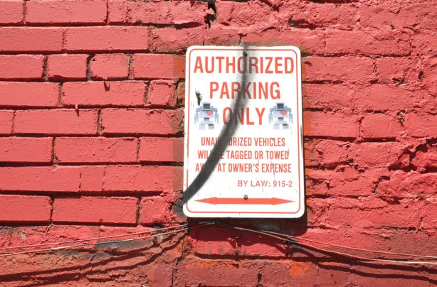 "A No parking sign on a very red wall.  Sign says ""authorized parking only"" and someone has put 2 lovebot stickers on it."