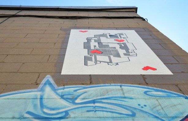 A wheatpaste lovebot of hearts playing card way up high on a wall