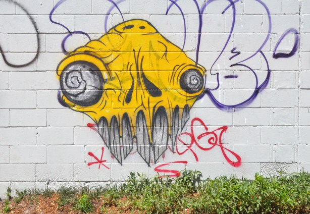 a yellow grominator graffiti painting, yellow with black and white bulging eyes