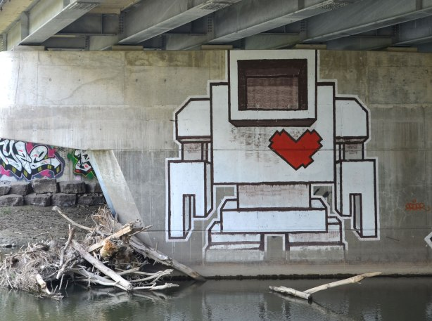 A large lovebot on a concrete support under a bridge by a river