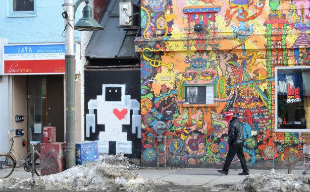 A painted lovebot about person height on a wall beside Lee's Palace on Bloor St - a building that is covered with intricate bright coloured pictures