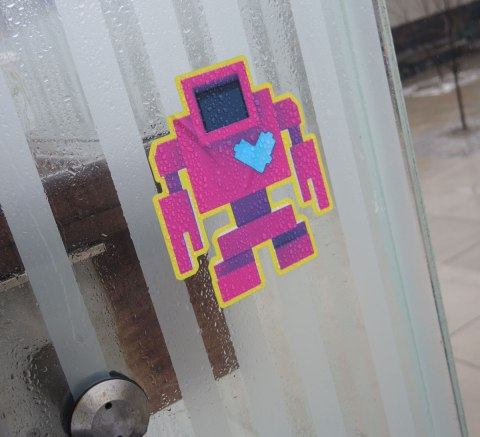 A pink and purple sticker lovebot on a glass wall