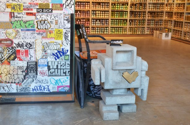 a little cement 3D lovebot statue stands on the floor of a store that sells cans of spray paint