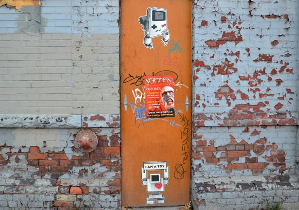 two small lovebots on an old orange door.