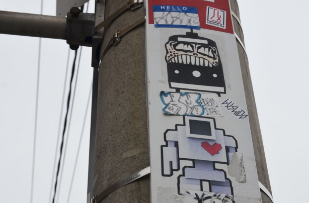 a lovebot sticker on a TTC bus stop pole