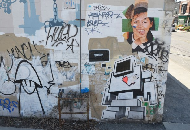 a lovebot wheatpaste along with some other graffiti and street art on a concrete wall