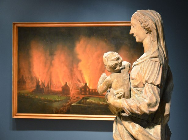 In the Art Gallery of Ontario, a wooden statue of Mary holding baby Jesus. Behind the statue is a large painting of the fire in Quebec City in the 1700's.