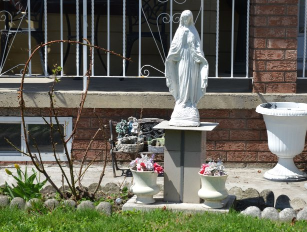 A small white statue of Mary on a makeshift pedestal in a front yard. Early spring, bare rose bush branches, a couple of small white planters with flowers in them. A white metal railing on the front porch.