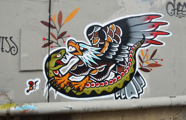 Street art painting of an eagle attacking a snake.