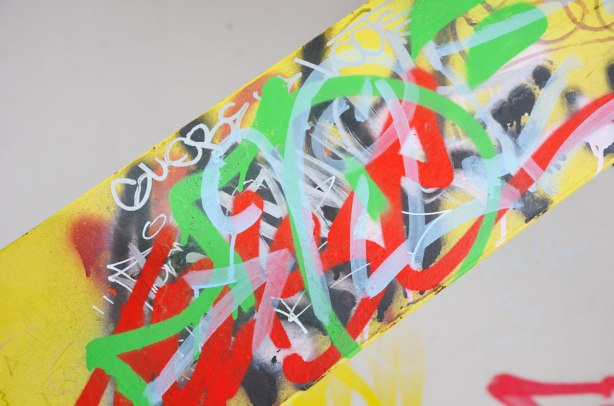 yellow metal girder covered with scribbles in black, red, and green.