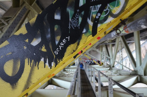 yellow girder in the foreground, the cat walk and metal structure of the bridge in the background.  Graffit on the girder including the word 'scarey' in white letters.