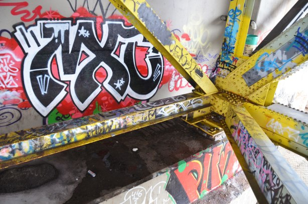 graffiti on the yellow girders under the bridge.  The concrete supports at the end of the bridge are also visible and also covered with graffit.
