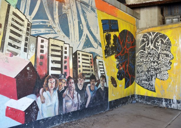 part of an old mural where the paint is starting to peel - a group of young people standing in front of some tall buildings as well as some head shapes with words on them.