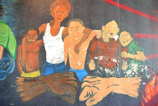 part of an old mural where the paint is starting to peel - a multiracial group of 5 young men also two fists coming together in the forground, one dark brown and one light brown.  The word respect is written on one of the arms.