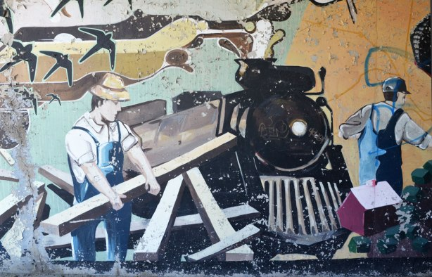 part of an old mural where the paint is starting to peel - a railway locomotive with a workman beside it.