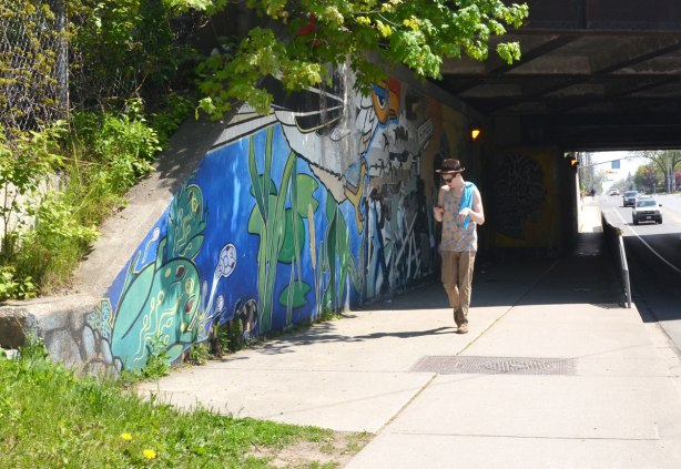 A man checks his phone while walking past a mural under a bridge