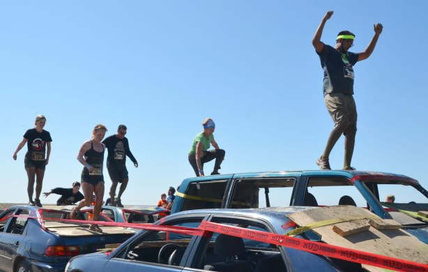A young man stands on top of a car with his arms upraised in triumph as he proceeds through an obstacle course