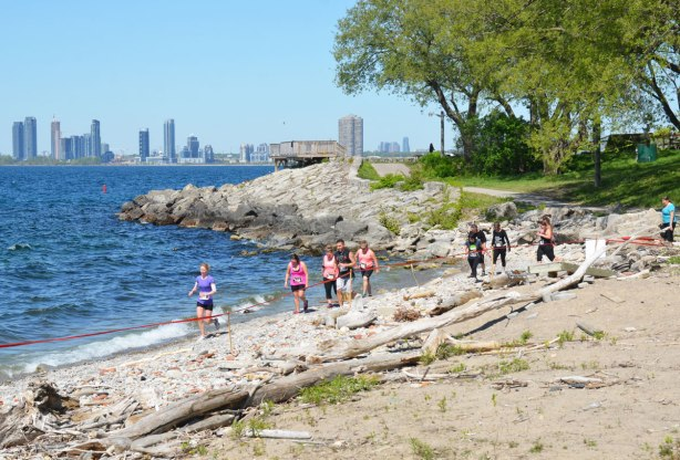 runners on the beach with the Mississauga skyline in the distance