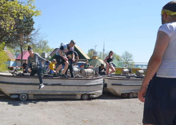 A man with his back to the camera watches team mates jump through, and off the side of, old wooden boats that were once part of a tourist attraction at Ontario Place