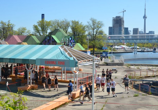 "runners in a race around Ontario Place go through the old ""loading zone"" area.  Toronto skyline and CN tower in the background."