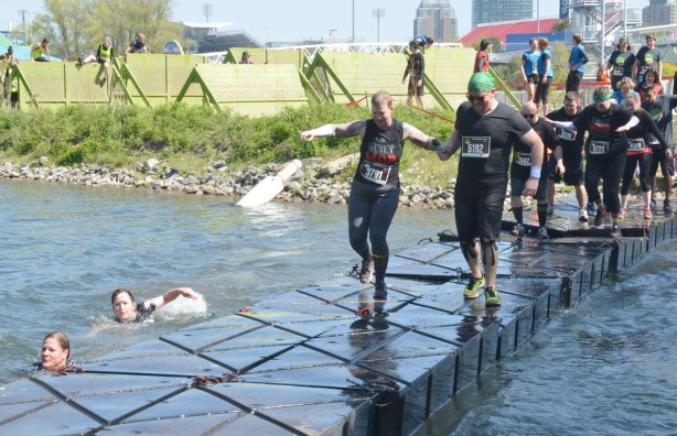 Two runners are holding hands as they cross a very tippy and wobbly floating bridge, many runners are behind them, waiting their turn to cross