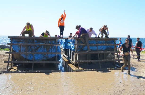 A race organizer in a bright orange jacket stands on a platform between two large tanks filled with muddy water as racers wade through the chest high water