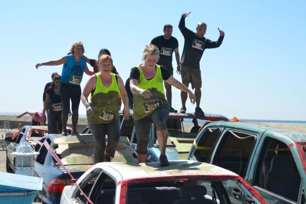 A group of people running over some wrecked cars as part of an obstacle race.  They are muddy.