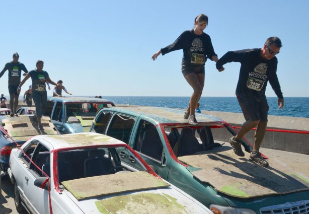 A couple holds hands while running across the roof of some wrecked cars