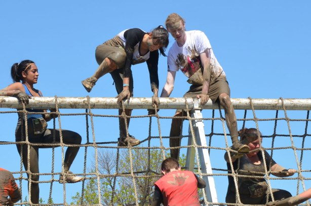 Competitors climb over the top of a very large and very tall rope climbing frame