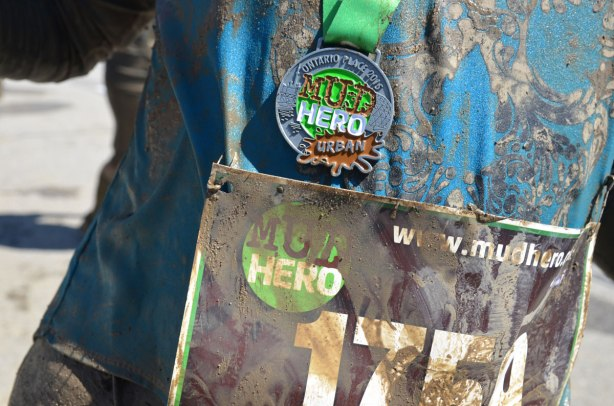 The front of a Tshirt on a competitor at the end of the Mud Hero race, along with the medal earned for completing the course