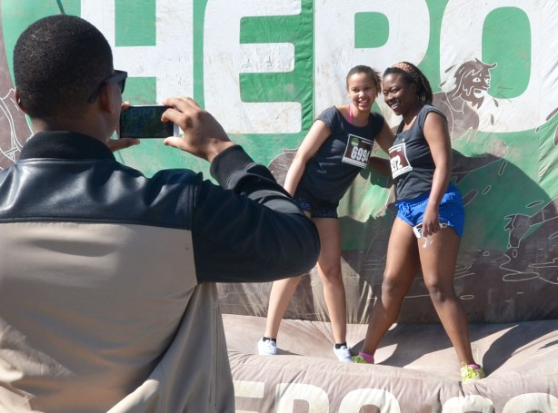 Two young women pose for the photo, being taken by a man whose back is to the viewer in this photo, before they start a race