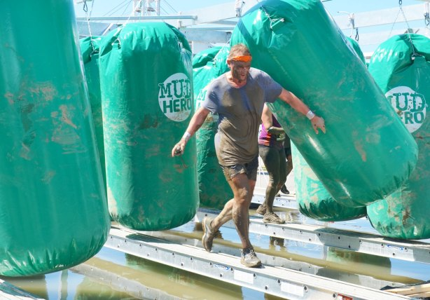A muddy man balancing on a metal beam as he makes his way past some large green punching bags